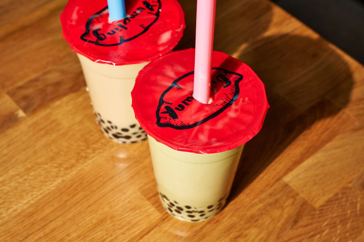 """Pastel-colored pink and blue straws pierce the red lids of two milk teas, whose lids have the word """"Yumpling"""" on them"""