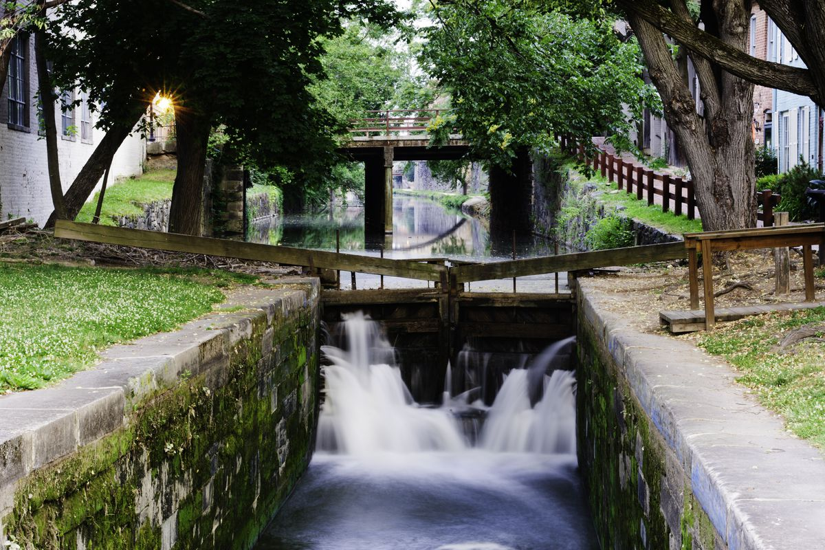 Water flows through a lock in a historic canal, which is lined by Federal-style homes.