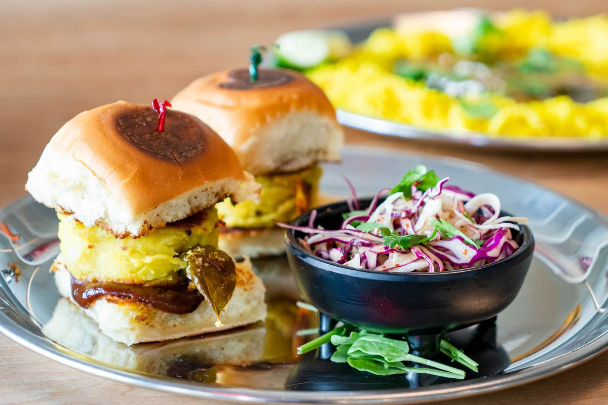 A closeup of aloo sliders with a side of cabbage.