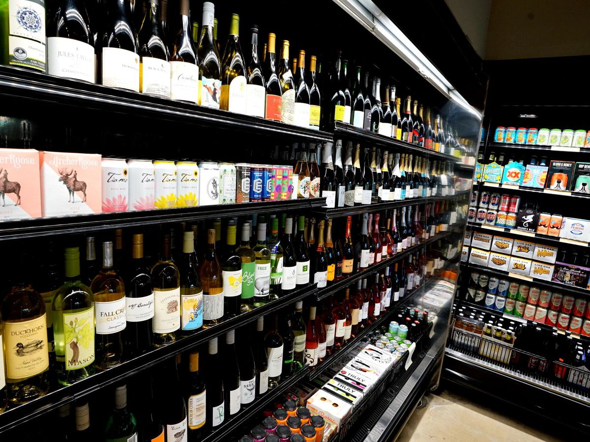 Open refrigerated shelves with bottles and cans of wines and beers