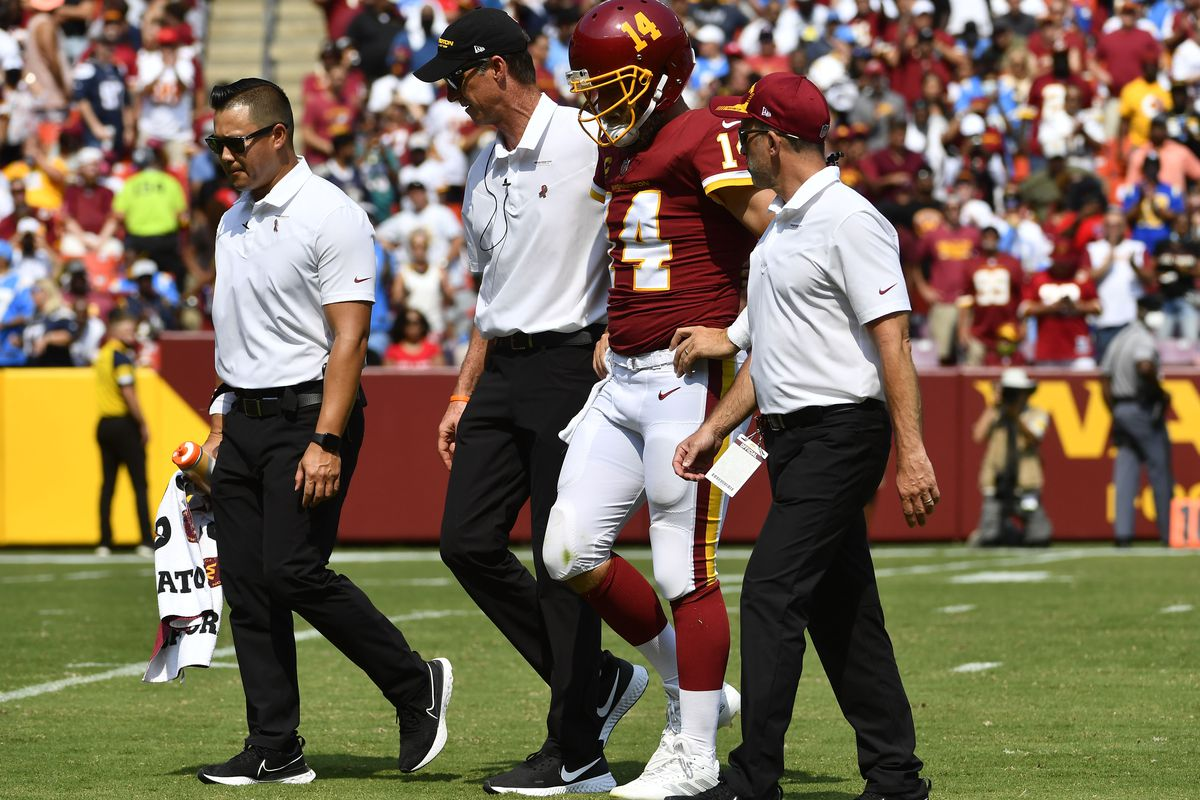 Washington Football Team quarterback Ryan Fitzpatrick (14) is helped off the field after suffering an injury during the second quarter against the Los Angeles Chargers at FedExField.