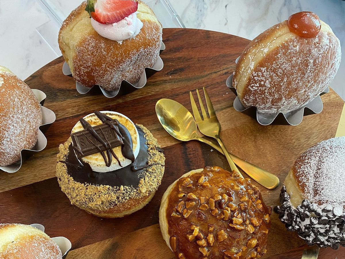 A variety of doughnuts on a wooden cutting board