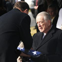 Utah Gov. Gary Herbert presents Myron Walker with an American flag during graveside services for Walker's wife, former Gov. Olene Walker, at the Salt Lake City Cemetery in Salt Lake City on Friday, Dec. 4, 2015. Walker died of natural causes at age 85.