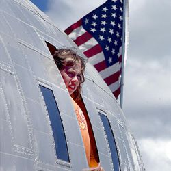 Jori Hancock stands at a window of one of the vintage planes on display as thousands turn out for the Hill Air Force Base air show  Saturday.