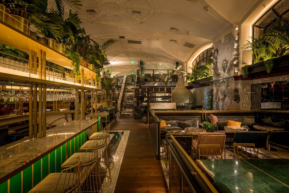 Deep green bar inside a historic building with loads of greenery.