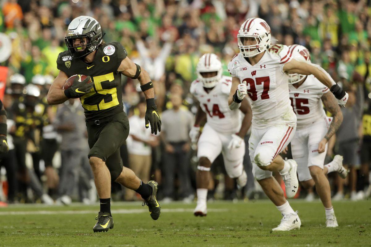 Oregon safety Brady Breeze, left, runs for a touchdown past Wisconsin running back Garrett Groshek