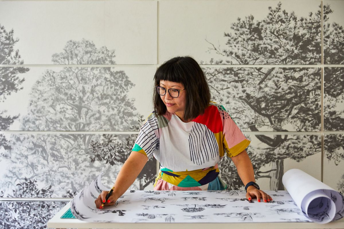 A woman drawing on paper.