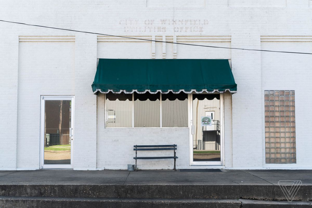 A storefront in downtown Winnfield, Louisiana where traces of removed lettering for the City of Winnfield Utilities Office can be seen above the door.