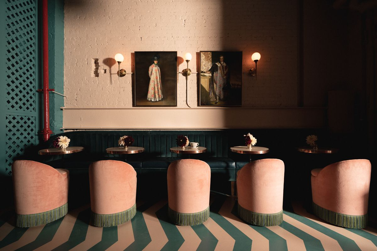 Velvet cushion seating and tables are partly occluded by shadows in the back of a cafe restaurant