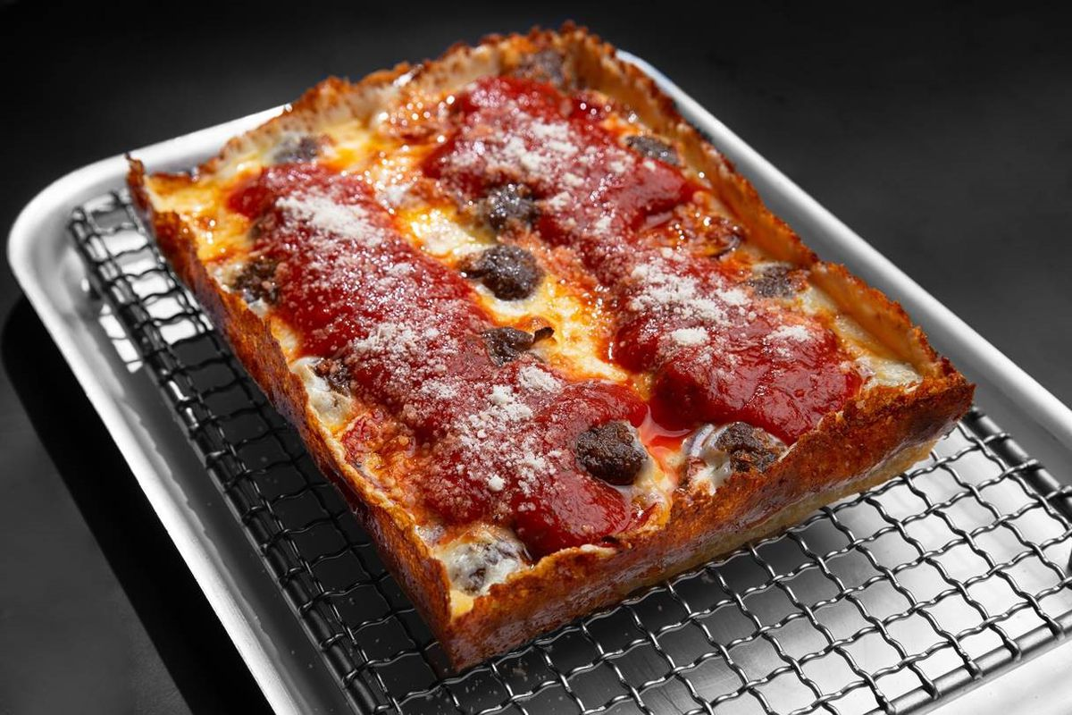A rectangular Detroit-style pizza sits on a steel pan on a dark background