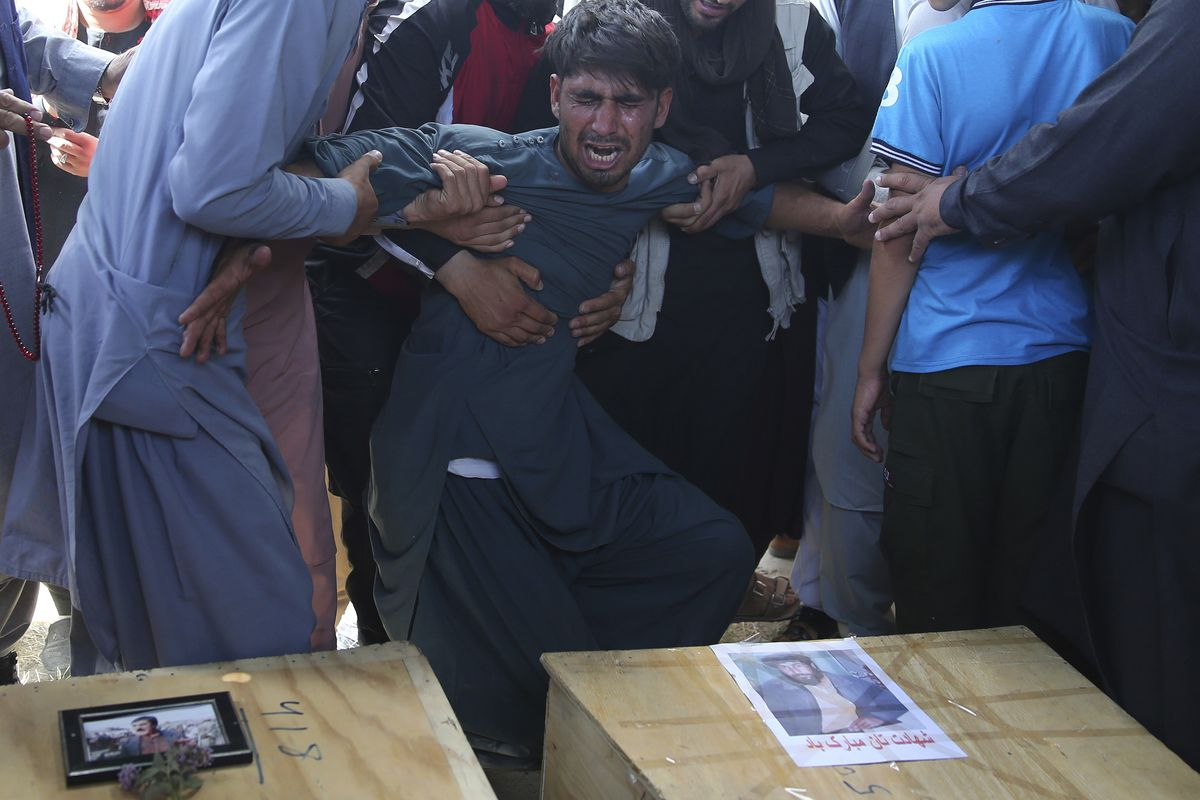 A relative wails near the coffins of victims of the Dubai City wedding hall bombing during a mass funeral in Kabul, Afghanistan, Sunday, Aug.18, 2019. The deadly bombing at the wedding in Afghanistan's capital late Saturday that killed dozens of people wa
