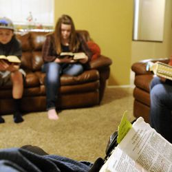 Clayton Hunt reads a passage from The Book of Mormon as his wife Kit, right, along with daughter Aspen (15) and son Christian (13) follow along in their home in Bountiful on Thursday, Dec. 26, 2013.