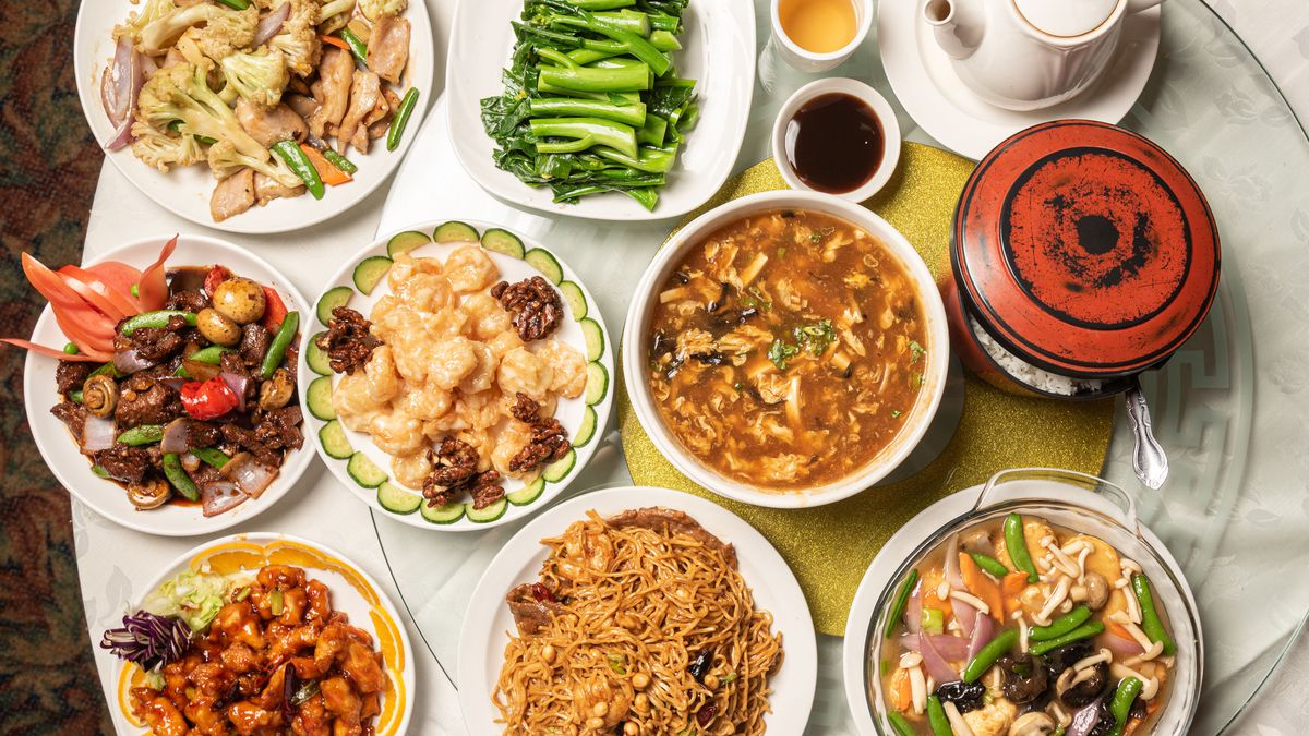 A table top brimming with Chinese food including vegetables, honey walnut shrimp, hot and sour soup, and more.