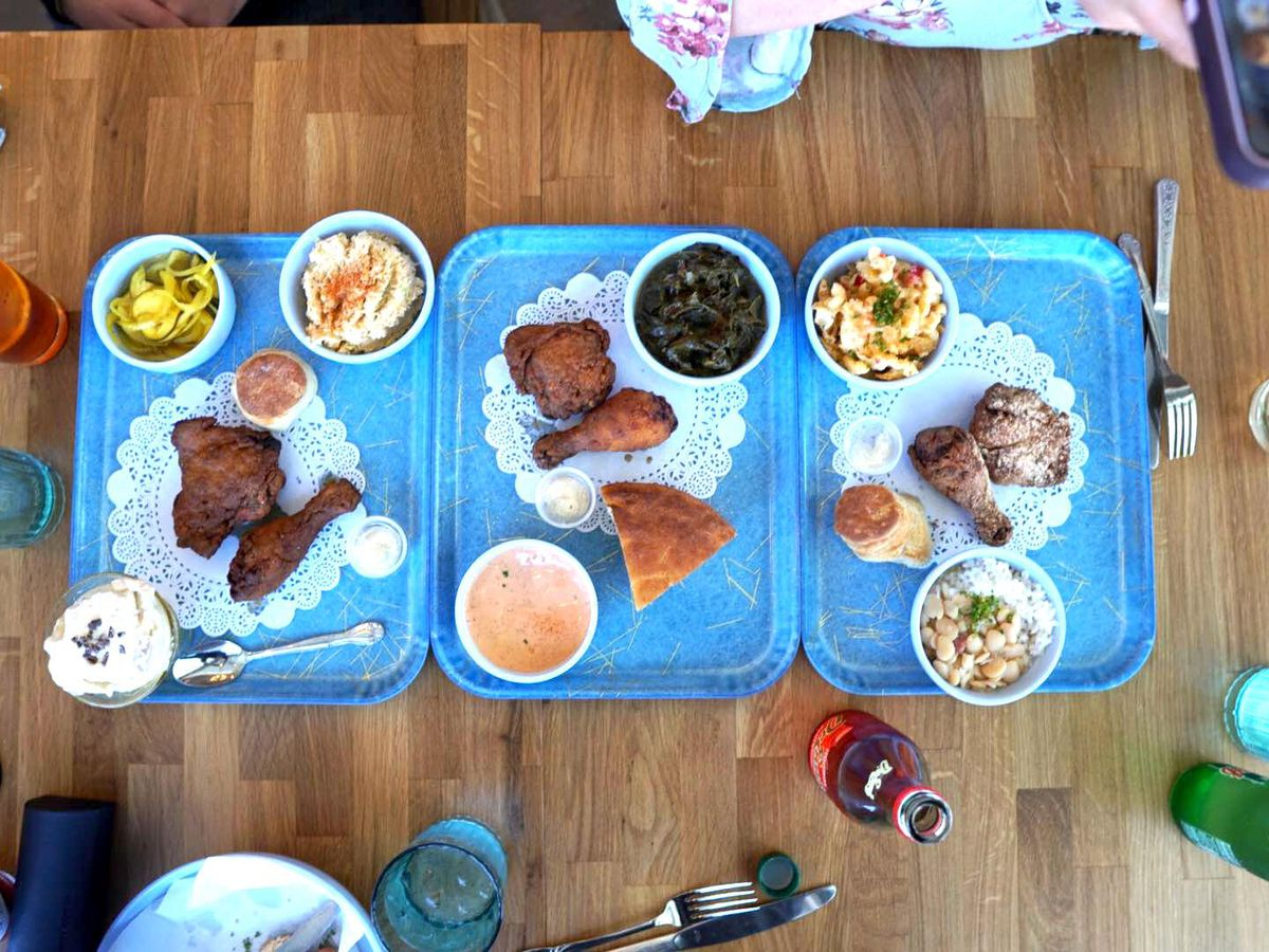 A picture of three Yonder platters with fried chicken, sides, and cornbread
