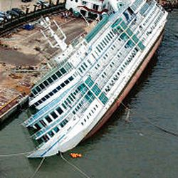 A cruise-ship-turned-hotel rests on its side in shallow water in Busan. It had been evacuated earlier and simply flipped over.