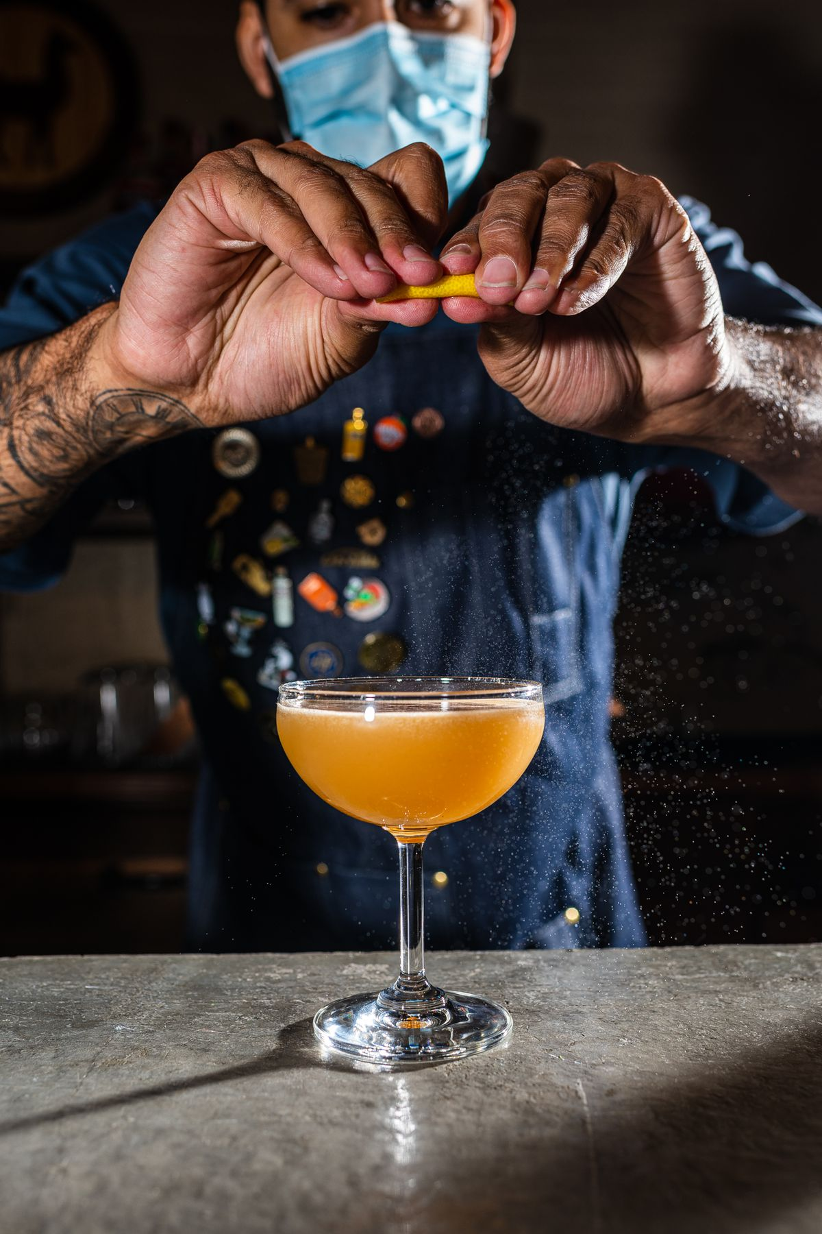 A bartender wearing a mask expresses a lemon peel into an apricot-colored aguardiente cocktail from Chacho