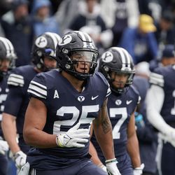 BYU players, including running back Tyler Allgeier (25), warm up before competing against Boise State during an NCAA college football game at LaVell Edwards Stadium in Provo on Saturday, Oct. 9, 2021.