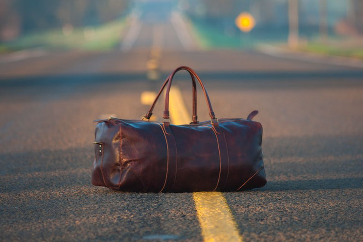 A brown leather suitcase sitting on the yellow hashed line of a sunny countryside highway