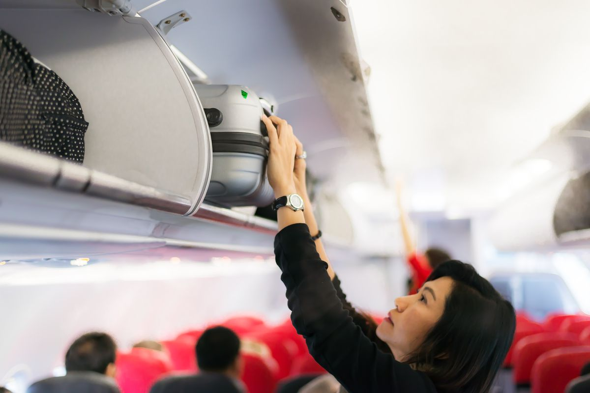 A woman attempts to store her luggage in an overhead compartment.