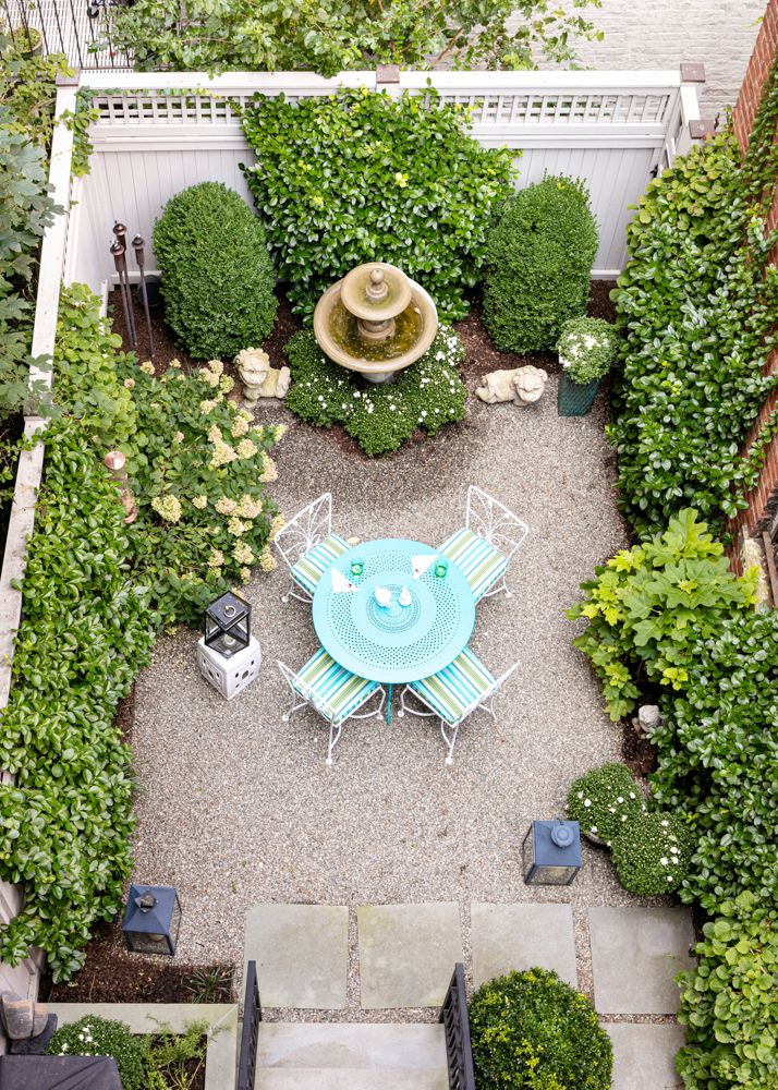 A garden with a round light blue table, four chairs, a white fence, and multiple plantings around it.