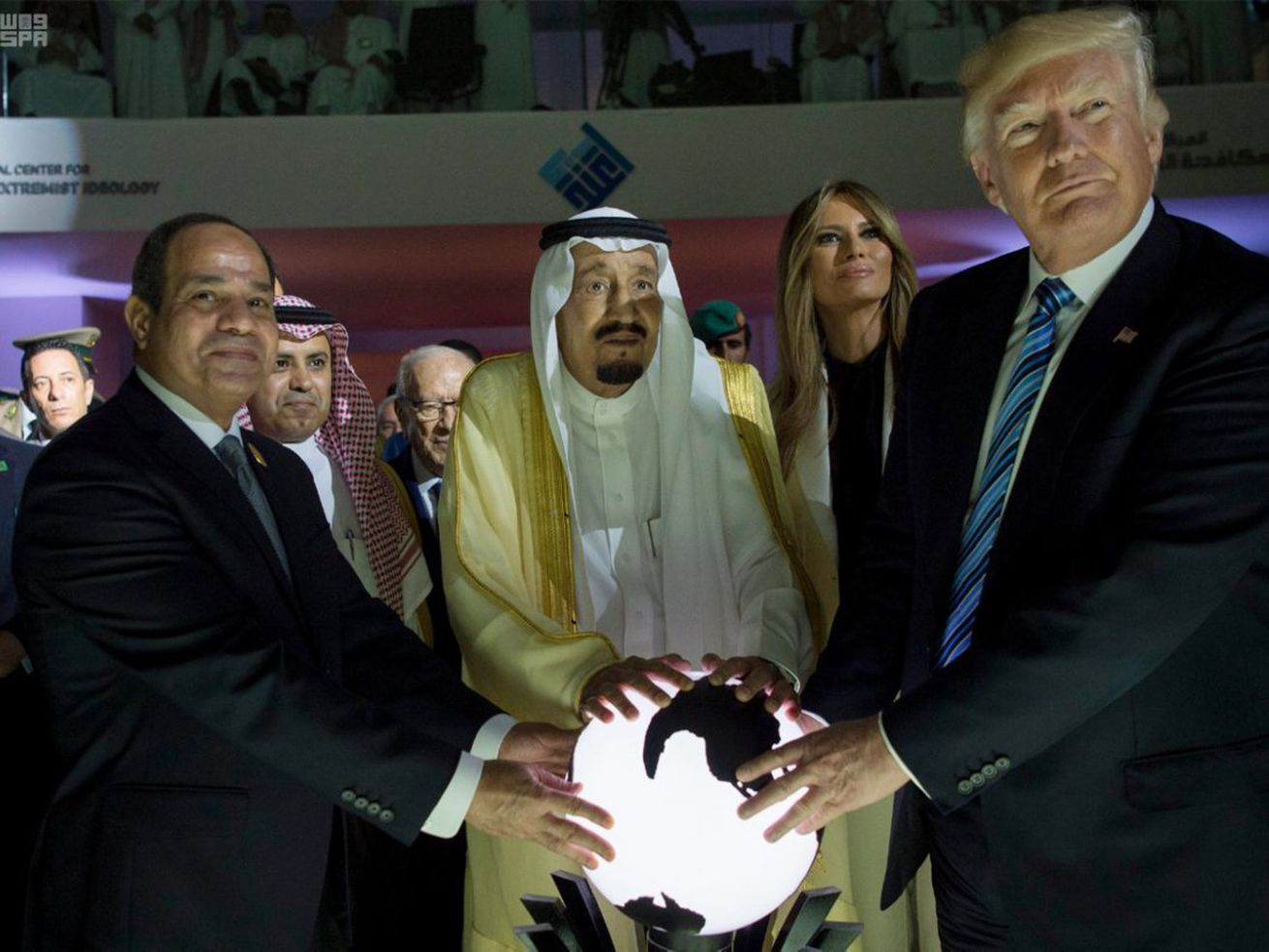 US President Donald Trump, Saudi King Salman bin Abdulaziz, and Egyptian President Abdel Fattah el-Sisi holding a glowing orb in a darkened room in Saudi Arabia.