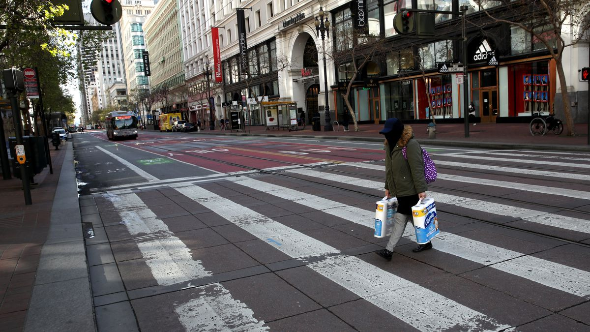 A women in San Francisco, wearing a face mask, crosses a deserted downtown street.