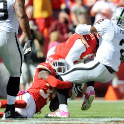 Oakland Raiders quarterback Terrelle Pryor (2) is sacked by Kansas City Chiefs outside linebacker Tamba Hali (91) and defensive back Quintin Demps (35) during the first half at Arrowhead Stadium.