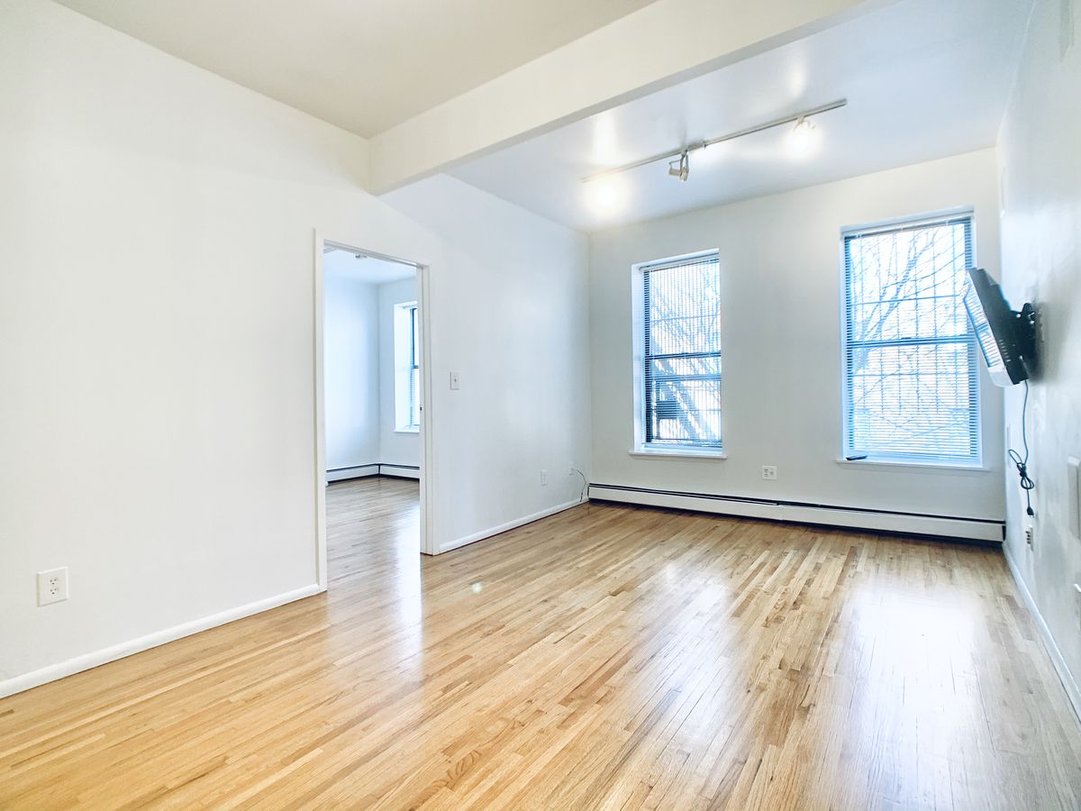 A bedroom with hardwood floors, two large windows, a TV hanging on the wall, and white walls.