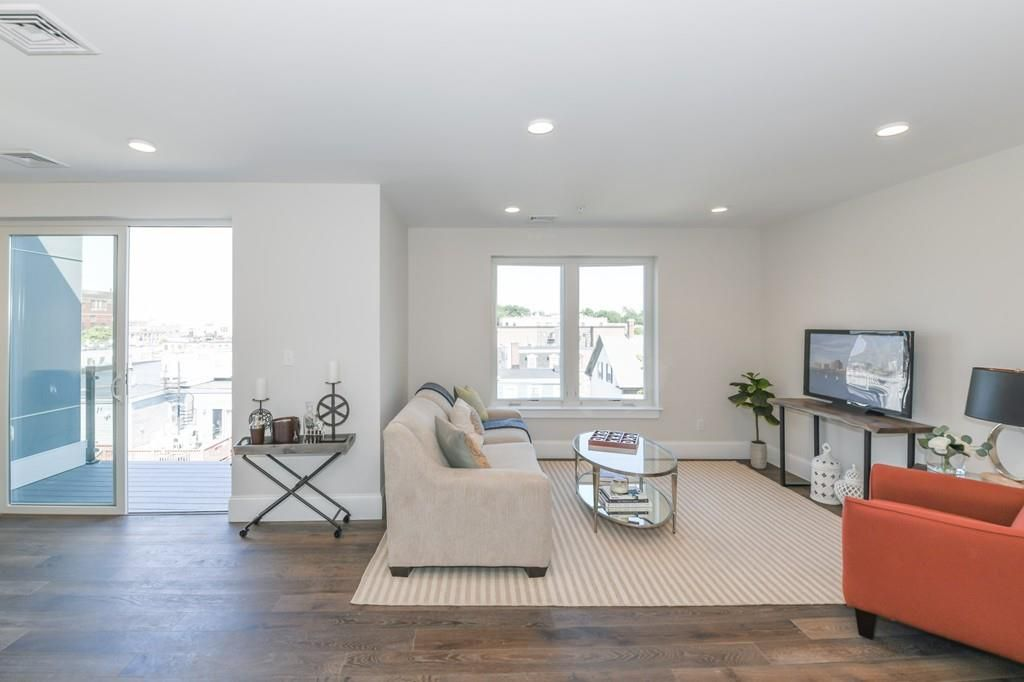 A spacious, airy living room with furniture in two-thirds and a sliding door to a deck on the last third.