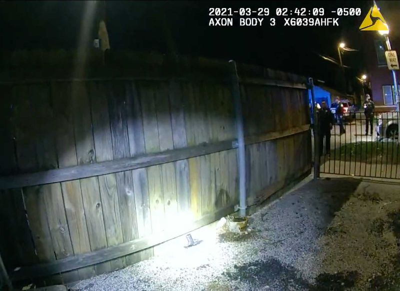 A gun is found along the fence line (via male officer's body camera)