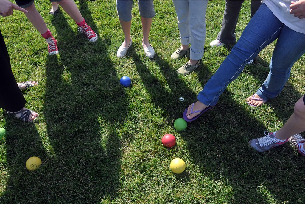 A group of people standing around some colorful bocci balls.
