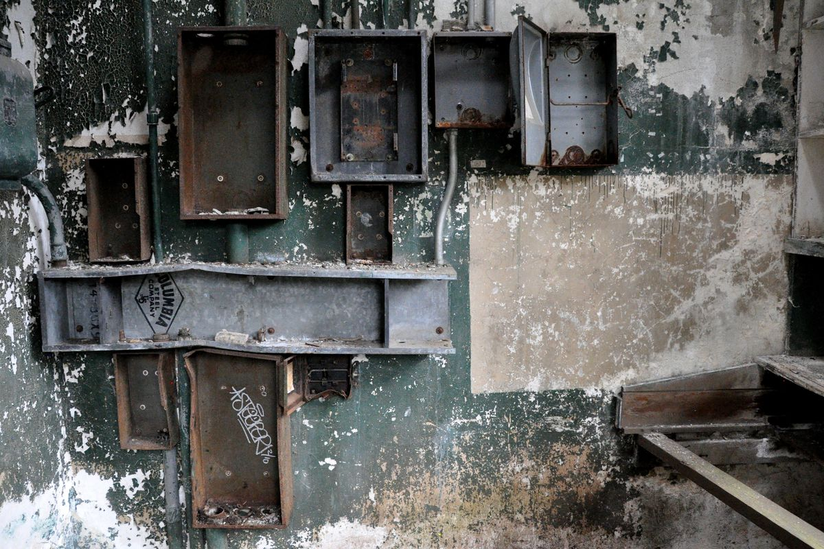 A series of deteriorating metal boxes are mounted on a wall with chipping, dull green paint. It's in an abandoned place.