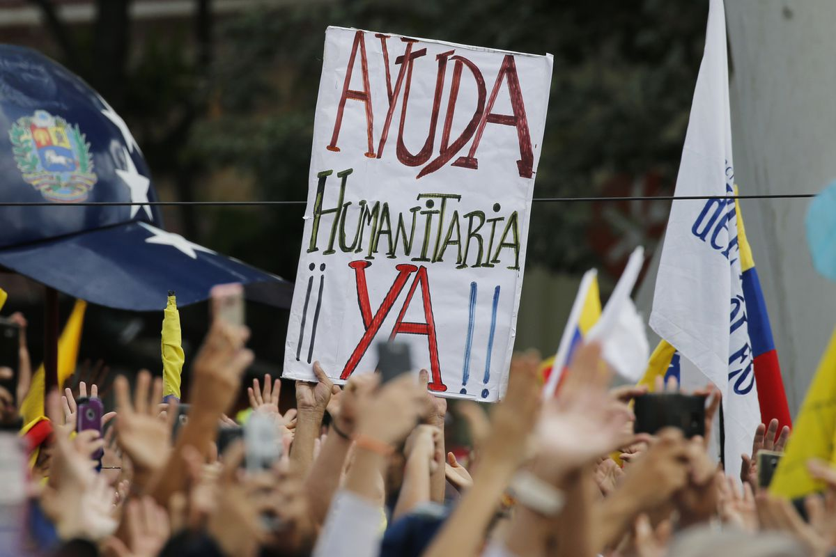 """FILE - In this March 4, 2019 file photo, a sign that reads in Spanish: """"Humanitarian aid now!"""" is held up during an opposition rally in Caracas, Venezuela. The sister organizations of the International Committee of the Red Cross, the International Federat"""