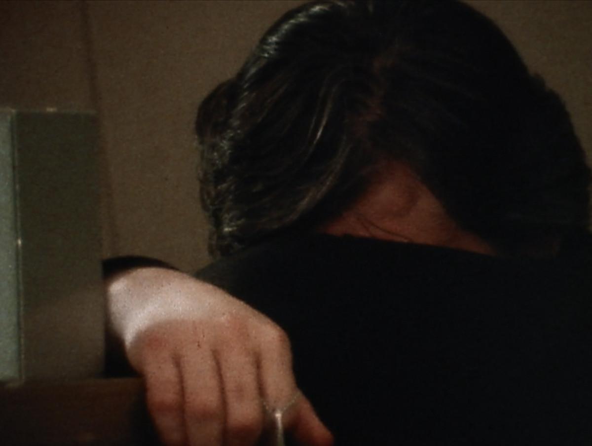 a man with dark hair buries his face