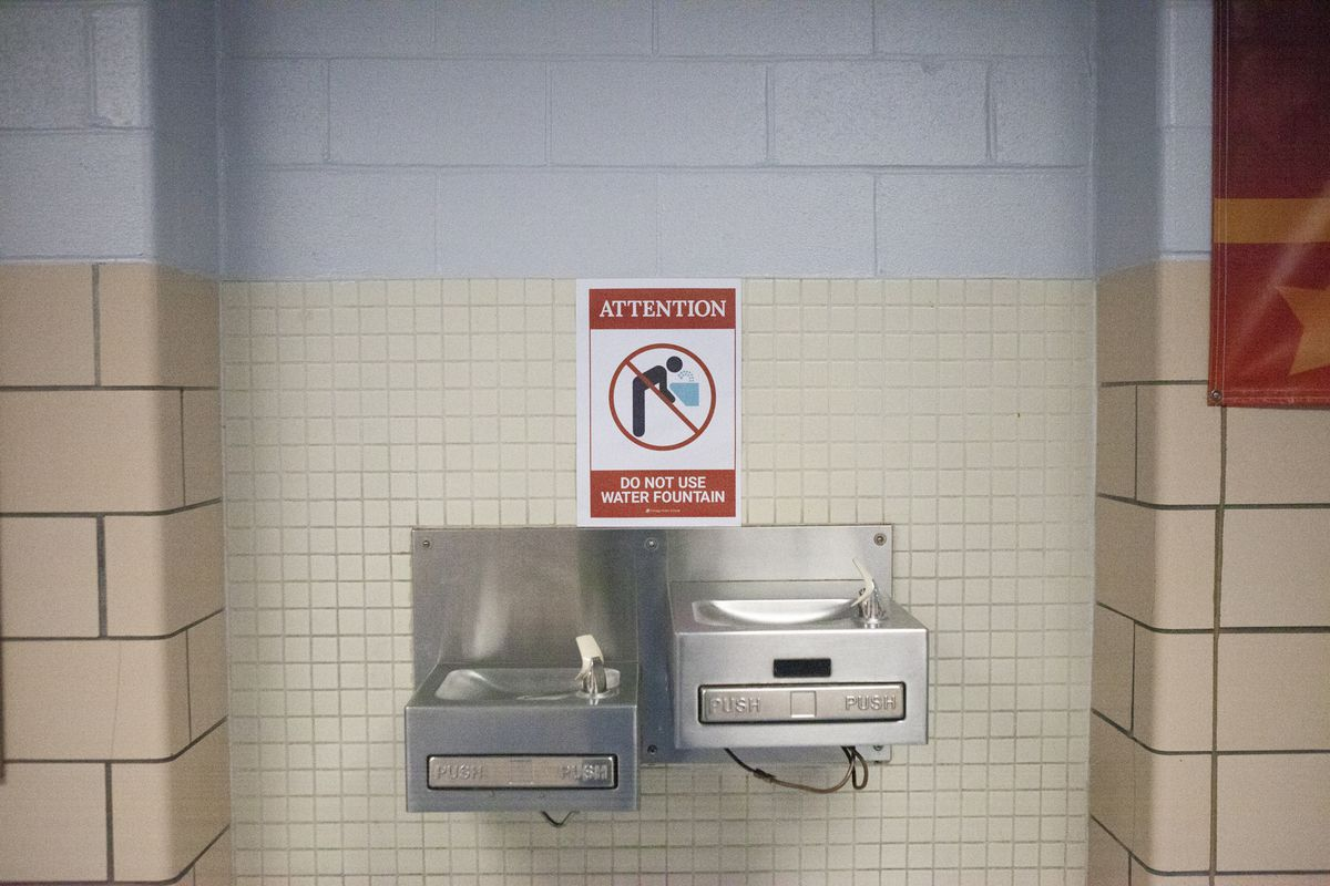 A sign between two water fountains that reads: Attention. Do not use water fountain.