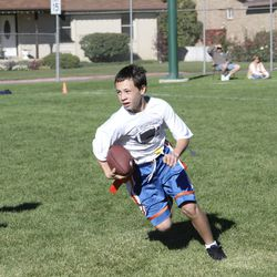 A flag-football-playing Britain Covey carries the pigskin during his youth.