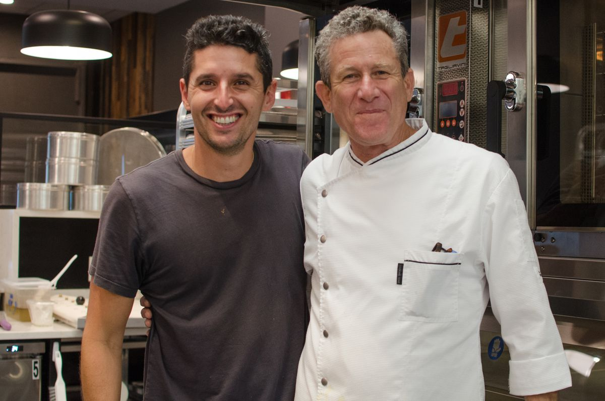 Two men stand next to each other, smiling, in a professional kitchen. One, in a black t-shirt, has dark, wavy hair; the other in a white chef's coat, has gray hair.