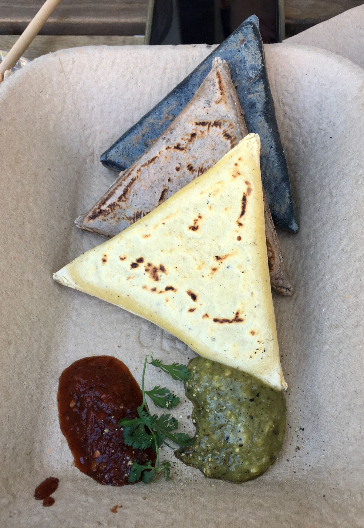 Three stuffed tortillas, shaped into triangles, sit in a cardboard to-go box beside pools of green and dark red salsa