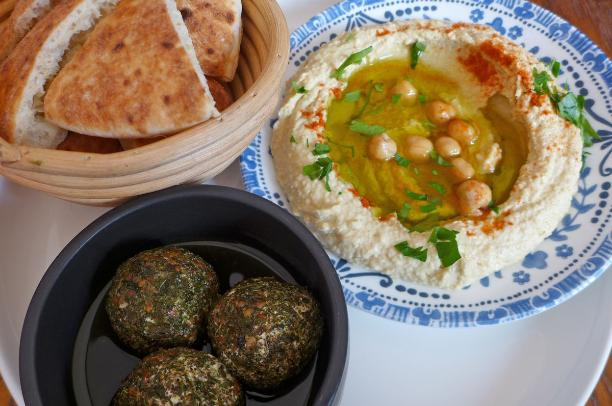 A basket of cut pitas in the upper left, plus a plate of hummus and chickpeas and three green orbs in a separate bowl.