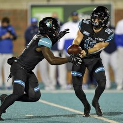 Coastal Carolina quarterback Grayson McCall, right, hands the ball off to CJ Marable during the first half of an NCAA college football game against BYU Saturday, Dec. 5, 2020, in Conway, S.C.