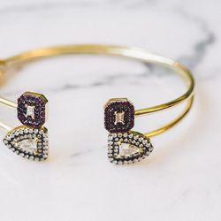 18 karat gold 'Privé' diamond baguette bangle with blackened ruby pavé, $5,985; 18 karat gold limited edition bangle with diamond bullets, $10,710