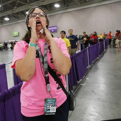 Salt Lake Comic Con volunteer Kaili Landon directs attendees during the convention at the Salt Palace in Salt Lake City Friday, Sept. 5, 2014.