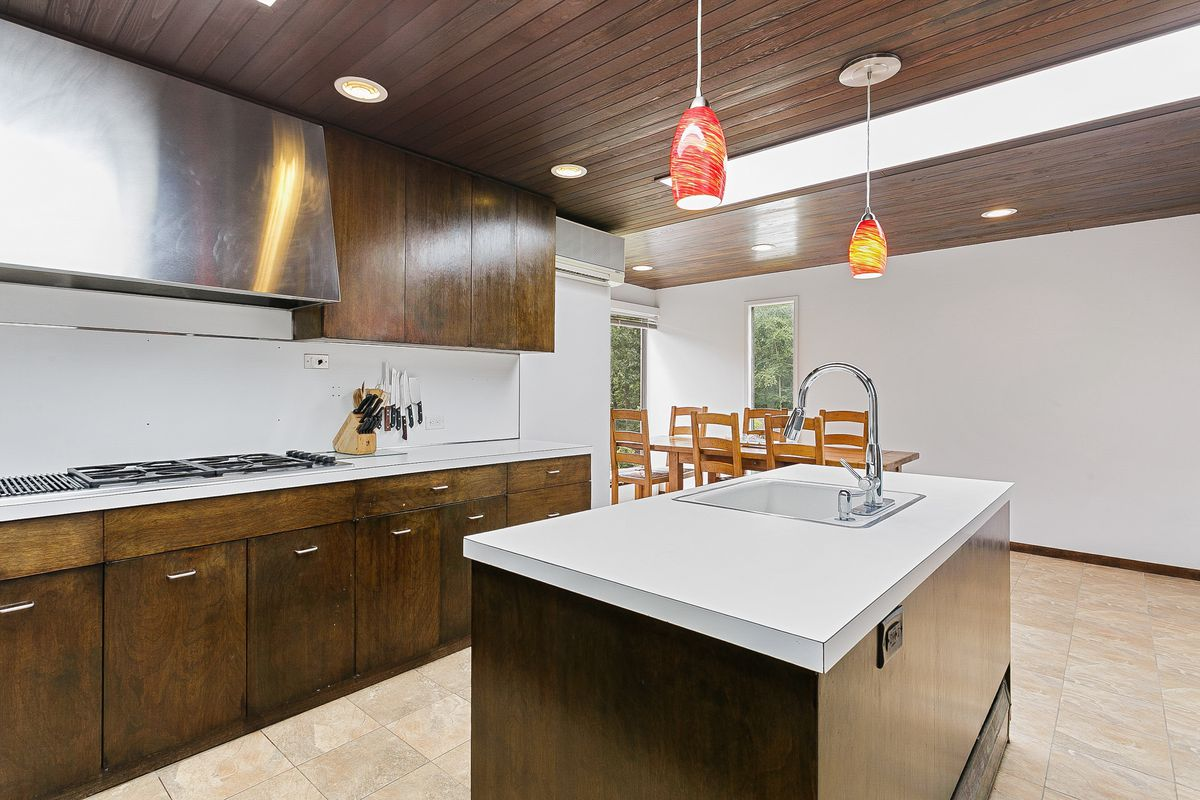 A kitchen with white countertops and dark brown cabinets.