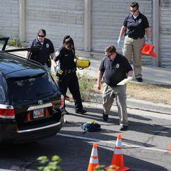 FILE - Crime scene investigators begin their work as Sandy police investigate a deadly shooting on Tuesday, June 6, 2017.