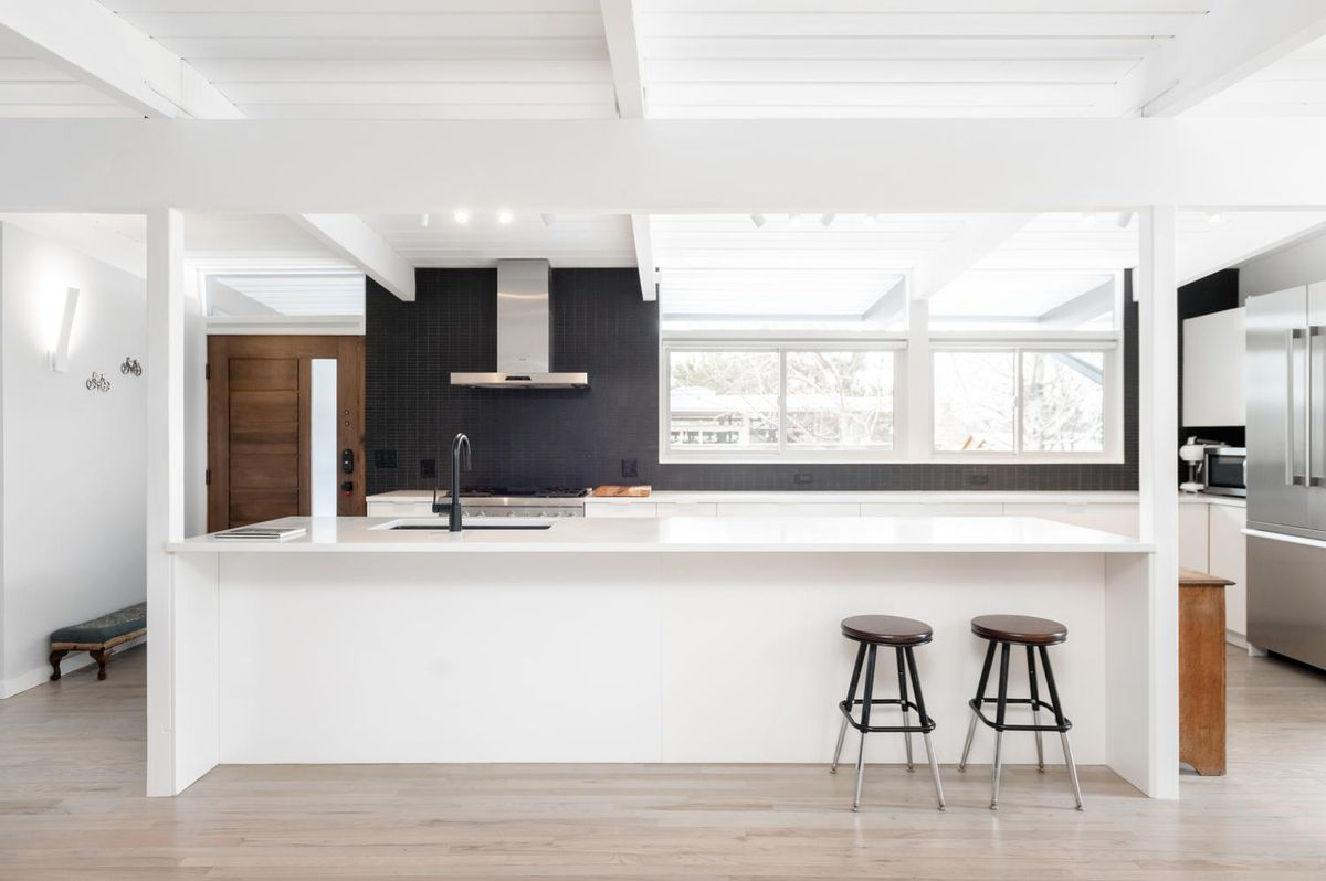A kitchen has a white kitchen island, black backsplash, and white post and beam ceilings.