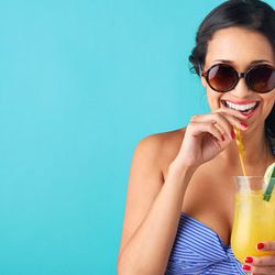 """Image via <a href=""""http://www.shutterstock.com/pic-173888171/stock-photo-happy-laughing-woman-wearing-a-bikini-drinking-a-tropical-cocktail-isolated-on-bright-blue.html?src=csl_recent_image-1"""">Jill Chen</a>/Shutterstock"""