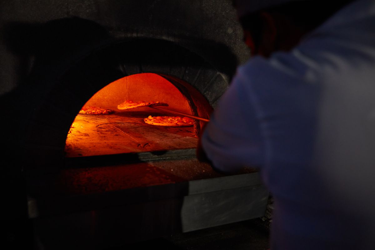 A chef checks on pizzas in a woodfire oven at night three of the Lexus Culinary Cinema in LA.
