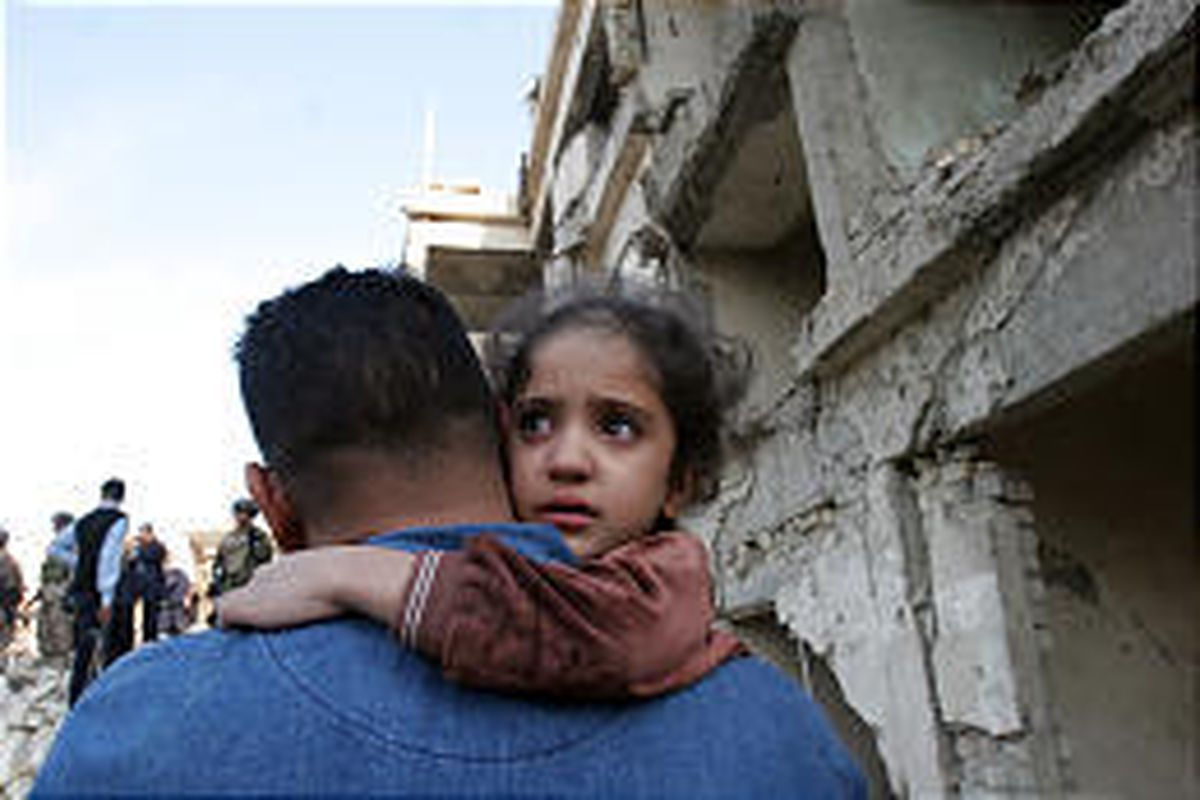 A child embraces her father near a building destroyed by two suicide car bombers in Baghdad on Nov. 18.