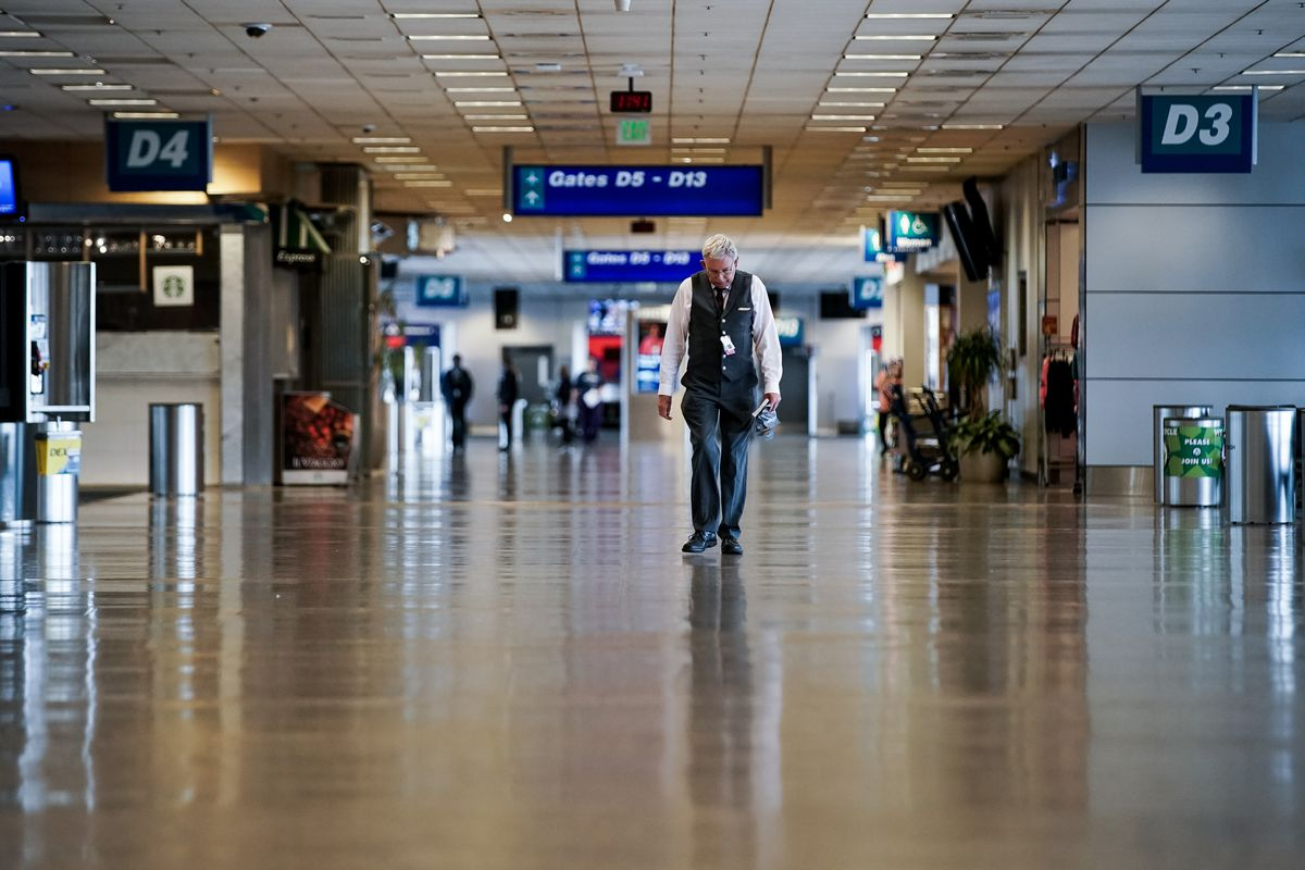 A Delta employee, who asked not to be named, walks through a nearly empty concourse in Terminal 1 at Salt Lake City International Airport on Thursday, April 30, 2020. Like airports all over the world, Salt Lake's airport has seen air traffic plummet due to the COVID-19 pandemic.