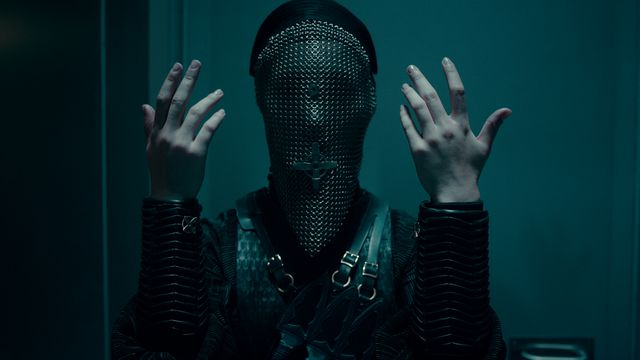 A warrior nun in a chainmail coif covering her face holds up her hands, palms inward.